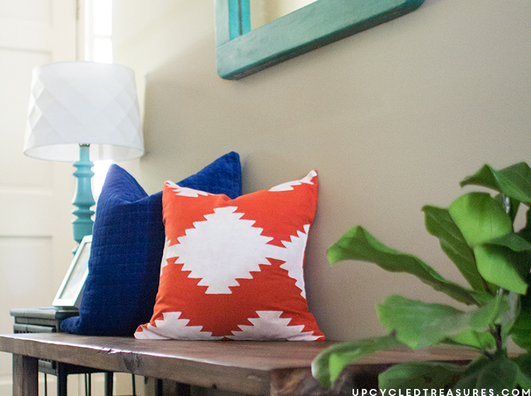 Kilim inspired painted pillow resting on bench in foyer. MountainModernLife.com