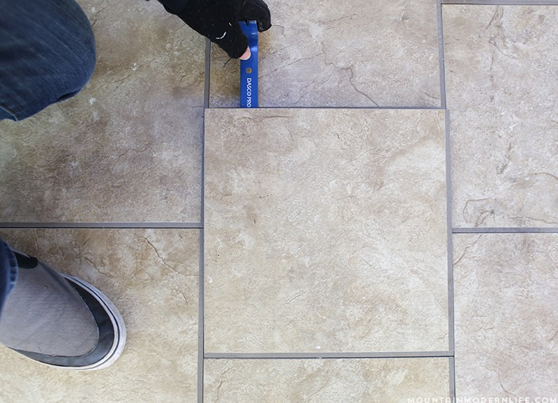 Removing the tiled flooring from the RV with a miniature crowbar | MountainModernLife.com