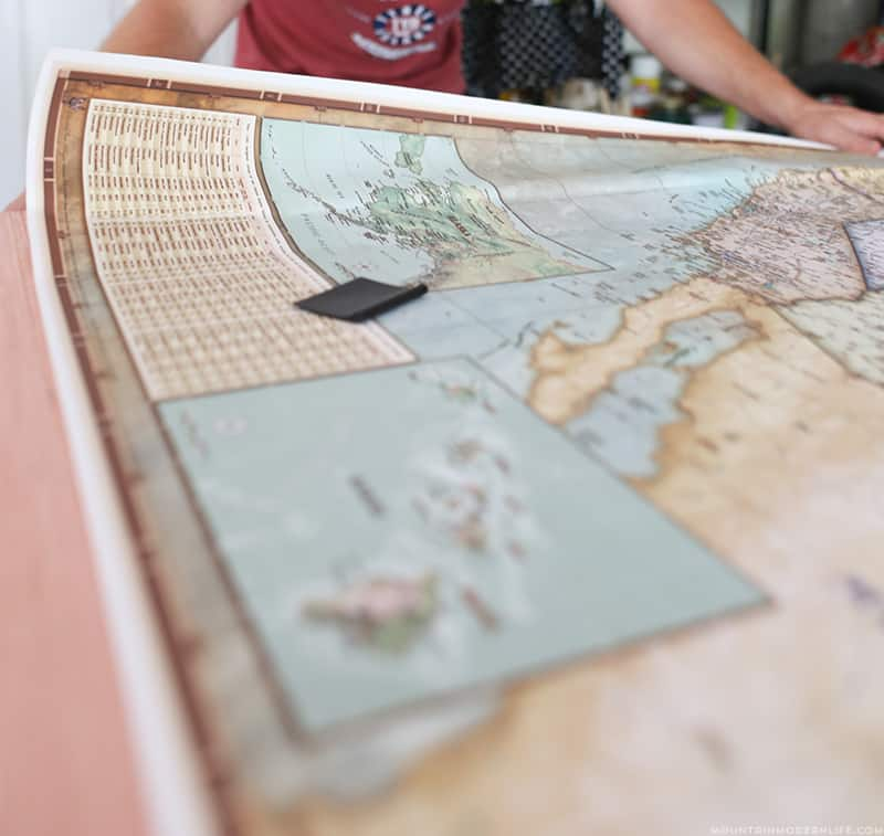 adding peel and stick map to piece of plywood