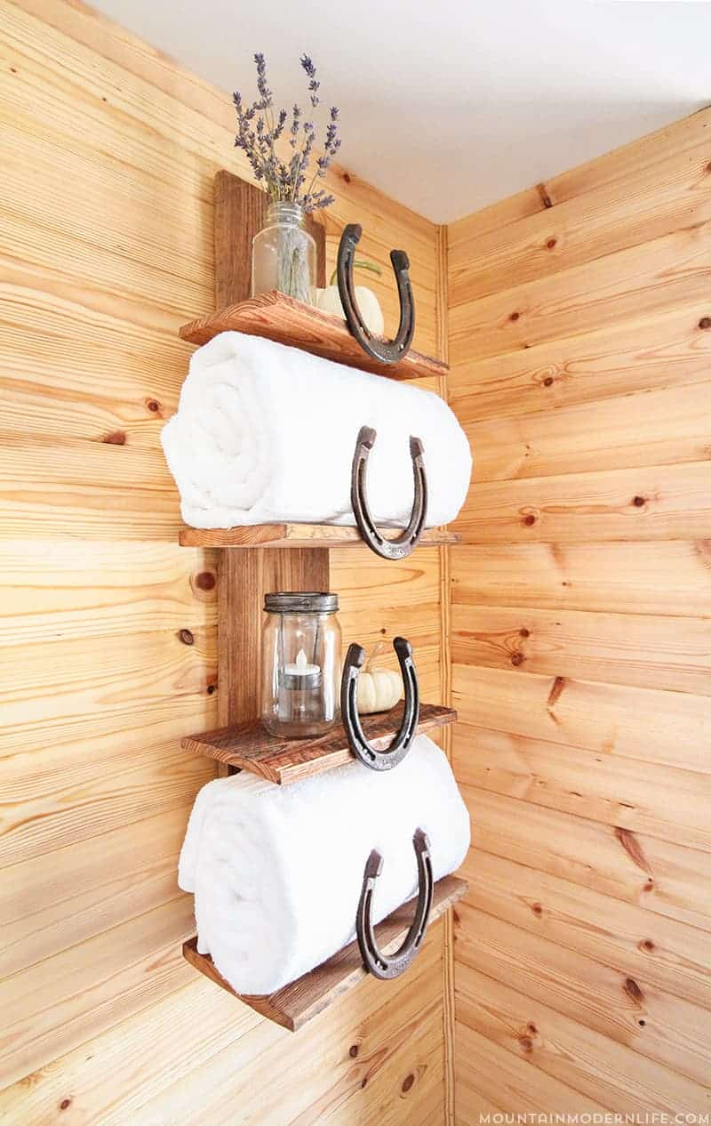 Organize your bathroom with this rustic bathroom shelf that uses horseshoes to keep towels and toiletries in place!