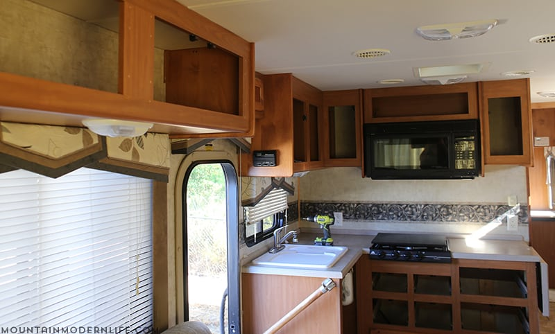 Planning to paint your tiny kitchen and considering using black? Check out these two-toned painted RV kitchen cabinets! MountainModernLife.com