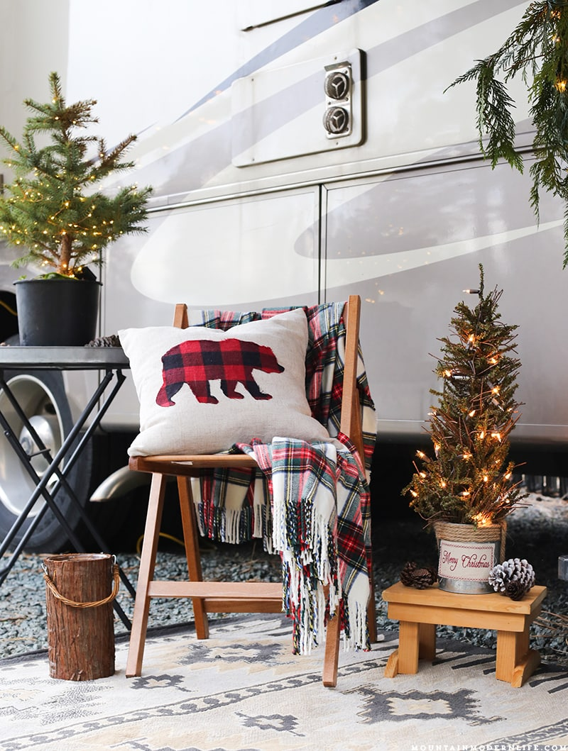 Bear pillow resting on chair outside the front of RV with Christmas decorations | MountainModernLife.com