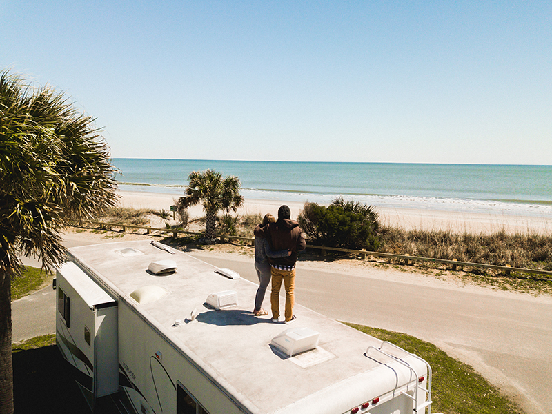 couple standing on roof of RV