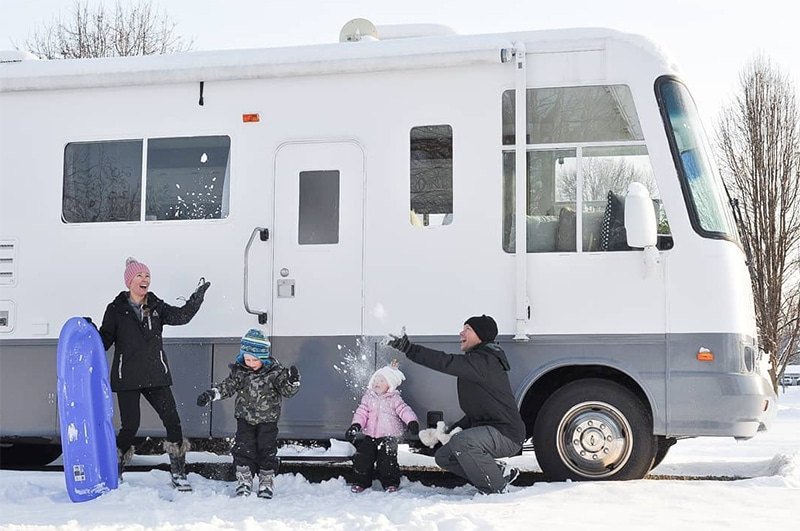 Family playing in snow outside of motorhome