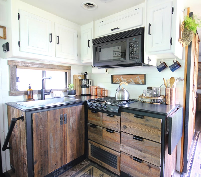 Considering adding black kitchen countertops to your home? Come see how we updated butcher block countertops for a rustic modern vibe in our RV. MountainModernLife.com #rvrenovation #rvremodel #rvkitchen #blackcounters #blackcountertops #rusticmodern #rusticmodernkitchen #mountainmodern #diycounters #tinykitchen #tinyhome #camperremodel #mountainmodernlife