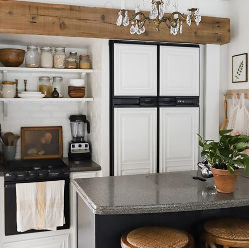 Tour this modern RV kitchen with old world charm from @r.maria.fuller that has wood beams that will make you swoon! See the before and after on MountainModernLife.com