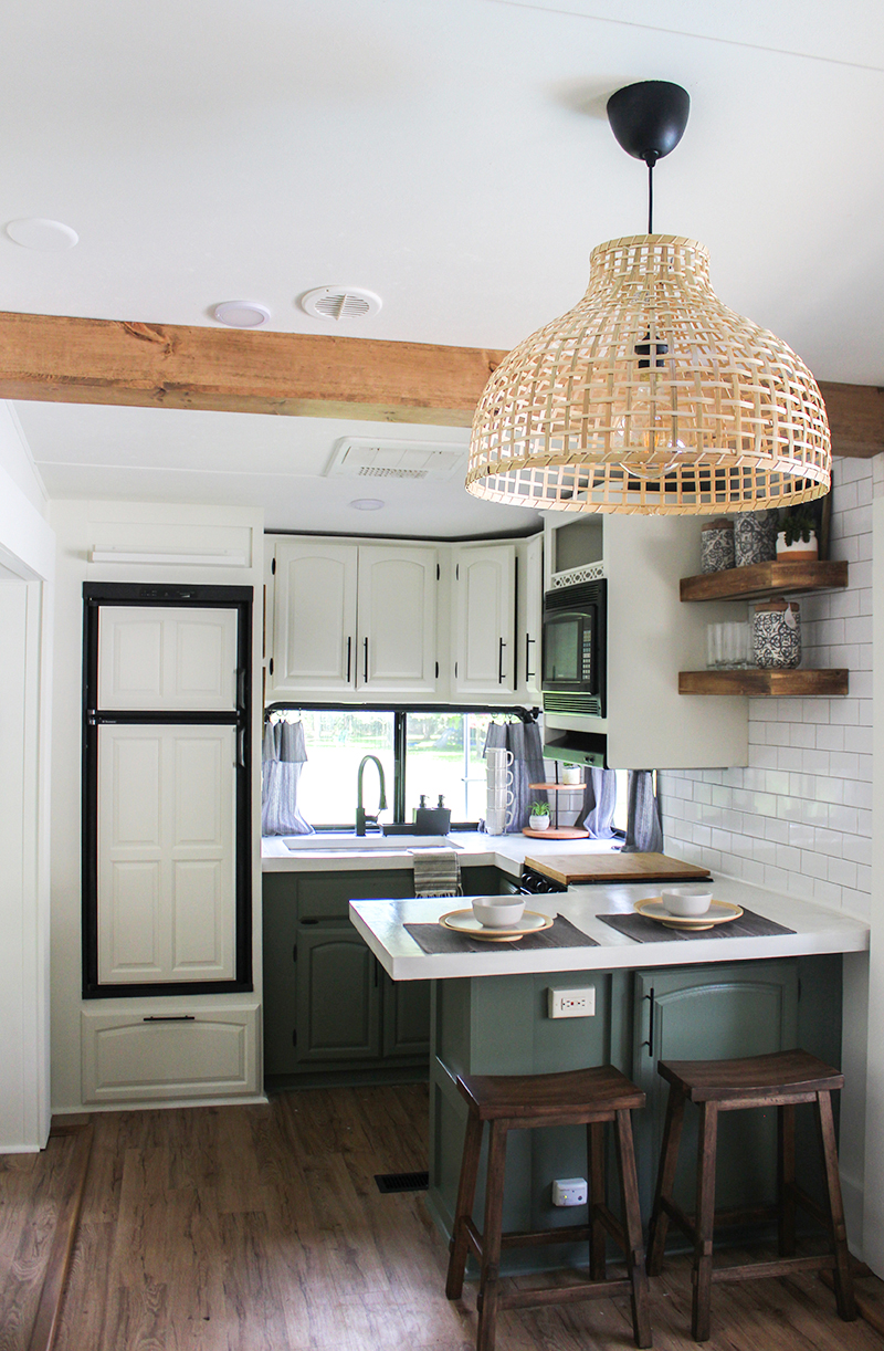 This remodeled RV kitchen has green cabinets and white concrete counters (and it's for sale!). Featuring @karleemmarsh on MountainModernLife.com