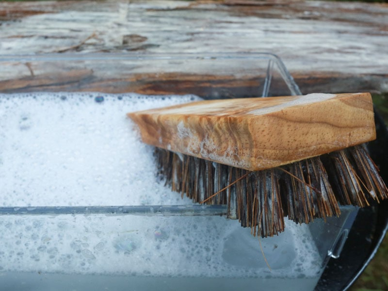 Cleaning reclaimed wood with bristle brush   MountainModernLife.com