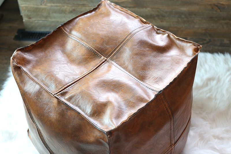 faux leather pouf that has been darkened with paint