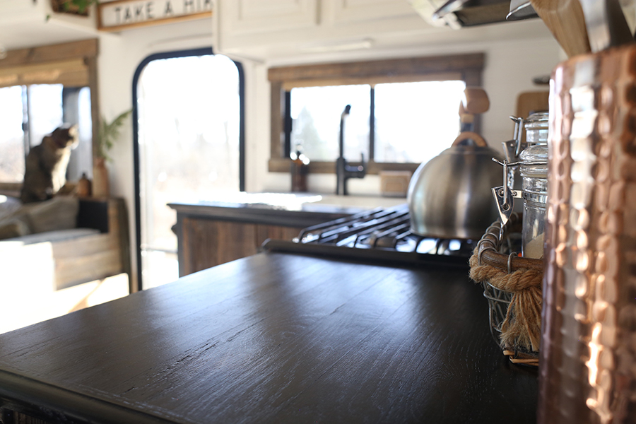 rustic rv kitchen with burlap roller shades