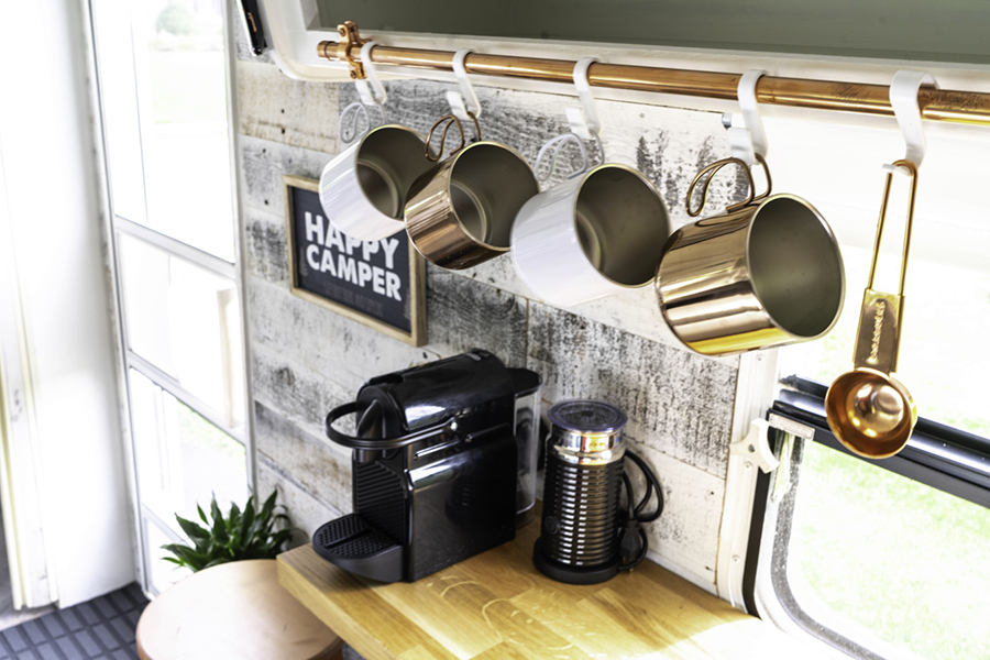 metal mugs hanging from copper pipe in camper