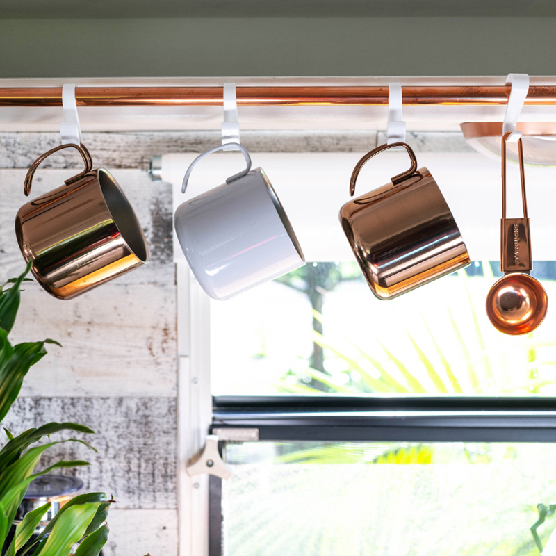 mugs hanging from copper pipe in camper