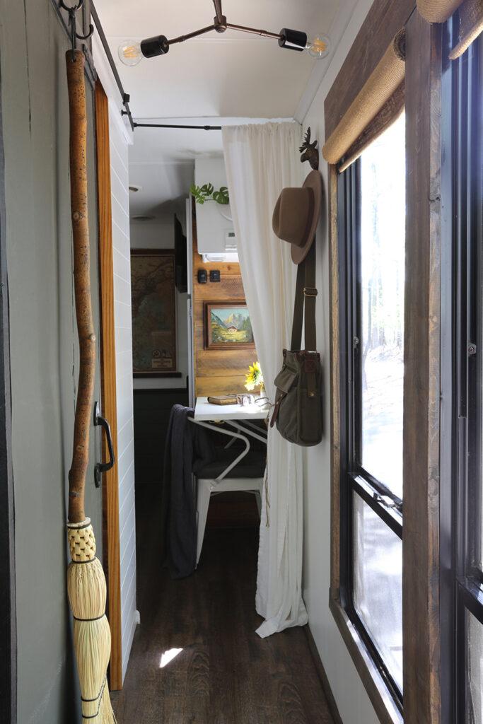 green sliding barn door in RV with handmade broom