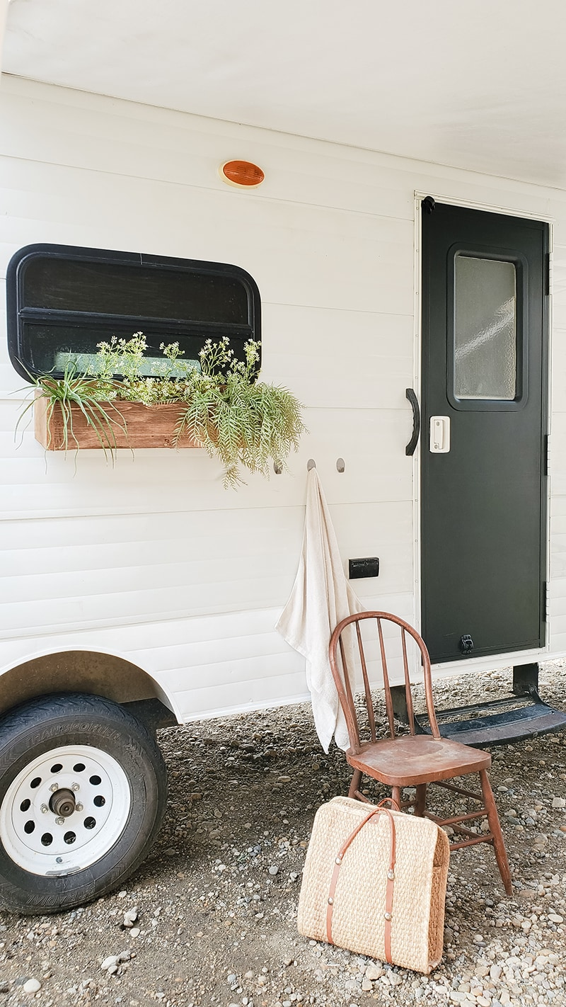 painted camper exterior with window flower boxes